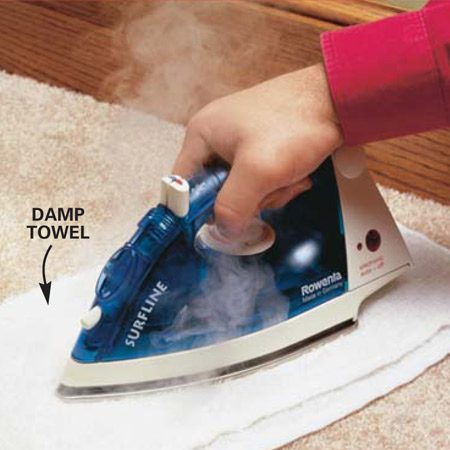 "<b>Photo 2: Iron the carpet</b></br> Dampen a white cotton towel, fold it in half and place it over the wax. Press an iron set on ""high"" over the towel for 10 seconds. The heat will draw the wax out of the carpet and into the towel. Repeat until the wax is gone (you may have to hold the iron in place for up to 30 seconds). If the towel dries out, rewet it, and if it becomes loaded with wax, grab another one."