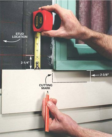 <b>Photo 8: Mark the siding to fit under windows</b></br> Hold the siding snug under the windowsill and mark the window edge location. Then measure from the chalk line to the top of the siding. Add 1/8 in. to your measurement. This is the width of the cutout.