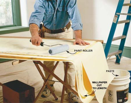 <b>Photo 4: Paste the sheet</b></br> Place the cut strips face down on the worktable. Paste the bottom half of a sheet evenly with a 3/8-in. nap roller, dipping it in a 5-gallon bucket with paste in it. Cover the edges by laying the upcoming strips under the one you're pasting; excess paste will be rolled onto the upcoming sheets. This will keep your worktable clean.
