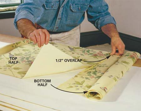 <b>Photo 6: Roll the paper up and set it aside</b></br> Roll up the bottom half loosely, slide the top half onto the table and spread more paste. Book the top half over so it overlaps the bottom edge by 1/2 in. Roll it up and allow the entire sheet to rest for the time specified by the manufacturer, about 10 minutes.