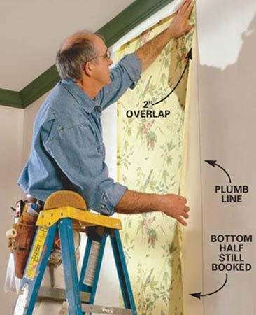 <b>Photo 7: Align the first sheet</b></br> Align the top half of the paper's edge to the plumb line, overlapping the ceiling molding by a few inches. Let the other edge hang loose to make positioning easier.