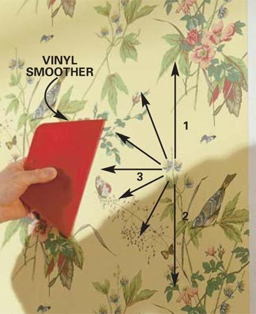 <b>Photo 8: Smooth the paper down</b></br> Pull a vinyl smoother across the paper. Move up and down along the plumbed edge, then diagonally away from it, to work out bubbles and wrinkles. Align and flatten the bottom half the same way.
