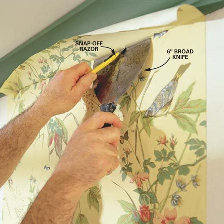<b>Photo 9: Trim the paper</b></br> Trim the overhanging paper with a sharp razor knife, using a 6-in. broad knife as a guide. Slide the broad knife across while leaving the tip of the razor in the paper till the cut is complete. Press just hard enough to cut through the wallcovering, not the drywall behind it.