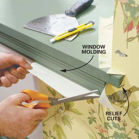<b>Photo 15: Cut around windows and doors in place</b></br> Trim the paper around window and door moldings by pressing it to the edge of the molding and making relief cuts with scissors and a razor until it lies flat to the wall. Using the razor, trim off the excess paper following the contour of the moldings. Guide your cuts with the broad knife on straight sections.