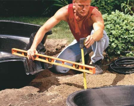 <b>Photo 7: Position the upper liner</b></br> Position the upper liner, again first digging an oversize hole, then placing it on a layer of sand to protect it. Make sure to provide a sufficient change in elevation so there's a strong, positive flow from upper to lower pond.