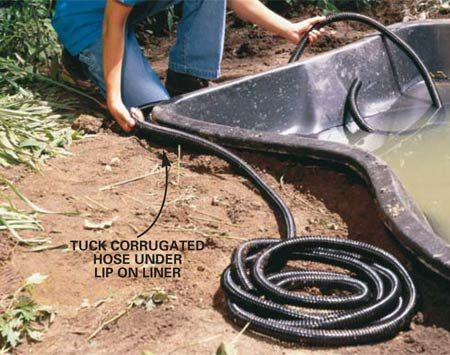 <b>Photo 6: Hide the hose</b></br> Tuck the hose connecting the upper and lower ponds under the lip of the shell. Continue to extend and protect the hose from kinks and pinches as you do the stonework around both ponds.