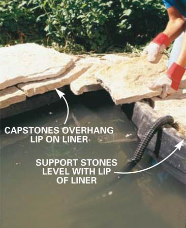 """<b>Photo 8: Start installing stone</b></br> Install the flagstone. Set the first support layer of stone level with the lip of the liner. Overhang the second """"cap"""" layer of stone to cover and disguise the lip of the liner."""