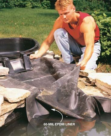 <b>Photo 11: Install the liner</b></br> Lay the rubber liner in place, draping it over the sides of the canal wall and into the lower pond. Tuck the liner up and behind the upper spillway. Use water from a garden hose to test flow and water tightness as you work.