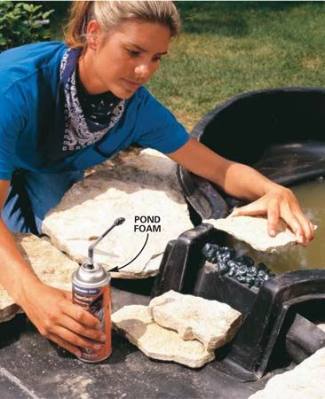 <b>Photo 12: Hide the spillway</b></br> Using special pond foam, attach thin layers of stone to conceal the plastic spillway. Complete the stonework around the upper pond.