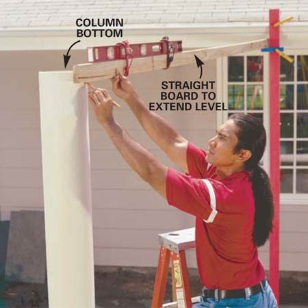<b>Photo 4: Mark the posts for cutting. </b></br> Attach a level to a straight 2x4 and mark the bottom of each post level with your height mark against the house. Remember, there's still 10-1/4 in. additional height going onto the tops of the posts.