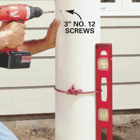 <b>Photo 8: Attach the columns to the posts</b><br/>Predrill and countersink eight screw holes in the sides of the columns: four 6 in.  from the bottom and four 30 in. from the bottom. Use 3-in. No. 12 exterior wood  screws to anchor the columns to the wood posts. Plumb the column as you screw  it to the post. You&rsquo;ll notice some play between the post and column. Opposing  screws will tighten the entire assembly.