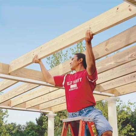 <b>Photo 12: Place the rafters on the ledgers</b><br/>Set the 2x8 flat rafters onto the ledgers (hold them perfectly vertical) and screw each end to the 2x10 beams with three 3-in. deck screws.