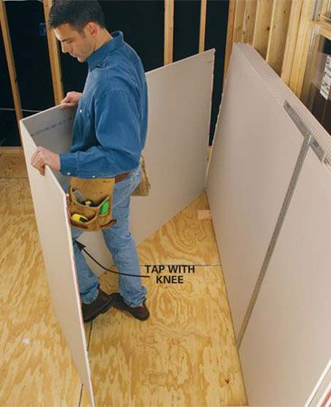 <b>Photo 3: Break the core </b></br> Lift one end of the sheet away from the stack and rest the sheet on the floor. A little knock from your knee will break the gypsum core so you can fold open the sheet.