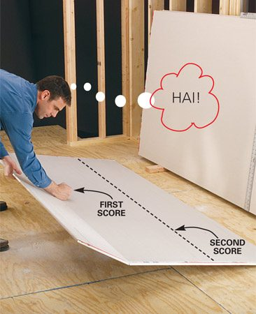 <b>Photo 8: Snap the sheet</b></br> Lower the sheet close to the floor and snap the cut open with a soft karate punch. Make sure the floor is clear of scraps and screws so you don't mar the face of the sheet.
