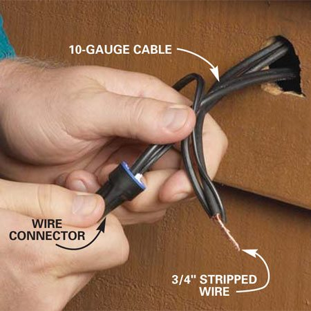 <b>Photo 1: Wire the fixture</b></br> Bore a 1-1/2 in. hole from the front side and pull a loop of the cable through. Cut the cable and rejoin the ends along with the light fixture leads with waterproof wire connectors.