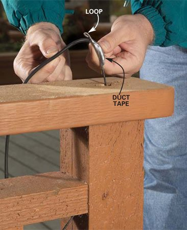 <b>Photo 6: Feed in the cable</b></br> Feed a heavy wire or electrician's fish tape through the holes in the post. Tape the circuit cable to the wire and pull it back through the holes. Connect the cable to the post cap light's feed wires with twist connectors.