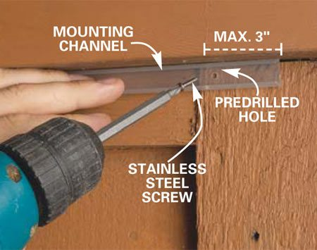 <b>Photo 10: Mount the track</b></br> Drive 3/4-in. No. 4 stainless steel screws through predrilled holes in the mounting track. Space the screws 2 ft. apart. Fasten the track within 3 in. of its ends.