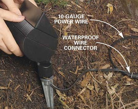 <b>Photo 13: Stake the floodlights</b></br> Install the floodlight by pushing the stake into the ground. Cover the wire and waterproof connectors with 6 in. of dirt.