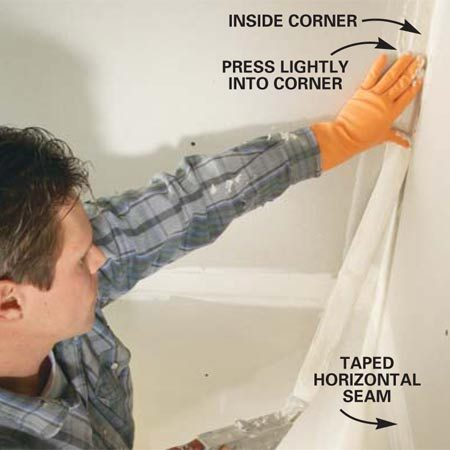 <b>Photo 7: Tape inside corners</b></br> CENTER the tape on inside corner seams and press it lightly into place with your hand.