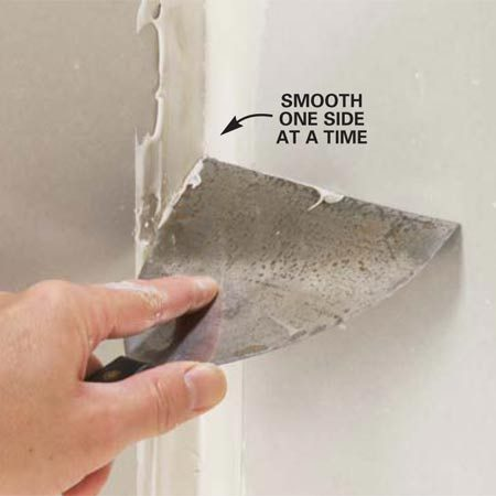 <b>Photo 8: Smooth one side of a corner</b></br> Smooth one side and then the other with your flexible taping knife. Run the side of the knife against the adjacent wall to guide it and create a straight, square corner.