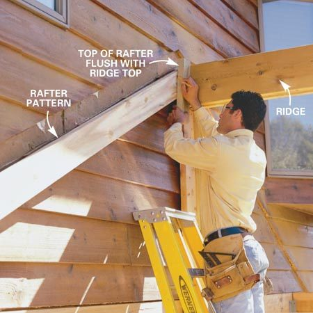 <b>Photo 10: Scribe the rafters</b></br> Cut an approximate 25-degree angle on the first 2x6 rafter and hold it in place against the ridge. Use a 2x4 to scribe the exact angle on the rafter. Use the rafter as a pattern to cut all the 2x6 rafters for that side. Repeat the process on the other side of the ridge.