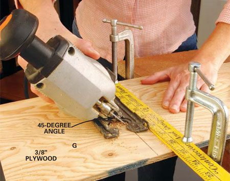 <b>Photo 3: Cut the roof pieces</b></br> Set your jigsaw base at 45 degrees and cut miter joints for the roof pieces G and H. Use a straightedge clamped to the workpiece as a guide for a perfectly even cut.