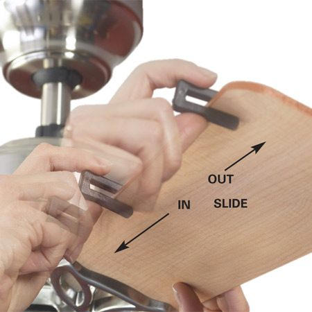 <b>Photo 2: Slide on the balancing clip</b></br> Slide the balancing clip on the trailing edge of any blade, halfway between the holder and tip. Run the fan to check the wobble. Repeat with each blade, noting which one most reduced the wobble, then slide the clip in small increments away from the center of that blade. Move the clip, operate the fan, then move it again until you eliminate as much wobble as possible.