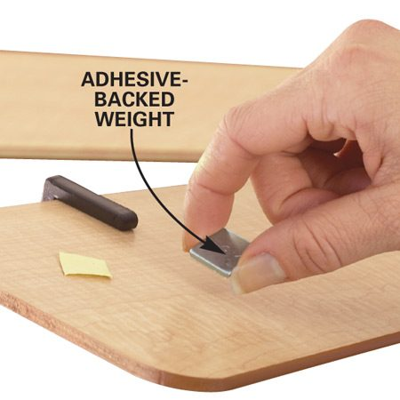 <b>Photo 3: Set a weight</b></br> Peel off the backing and stick the adhesive-backed balancing weight on the top center of the blade directly in line with the balancing clip.