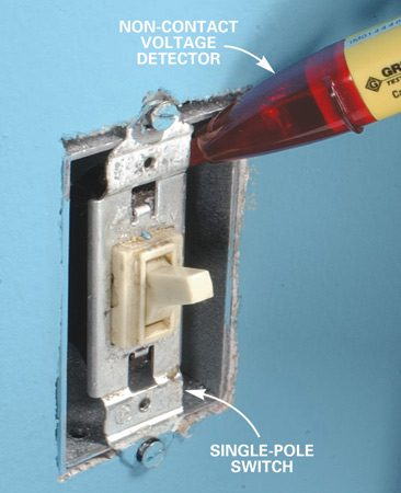 <b>Photo 1: Check for hot wires</b></br> Turn off the power at the main circuit panel. Hold the tip of a non-contact voltage detector near each screw terminal to be sure the power is off. Then unscrew the switch and pull it from the box.