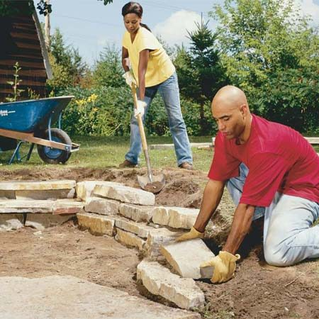 <b>Photo 10: Add a retaining wall</b></br> Build a small retaining wall by stacking smaller stones and filling behind them with dirt. Stagger the joints and step each layer back a couple of inches from the one below.