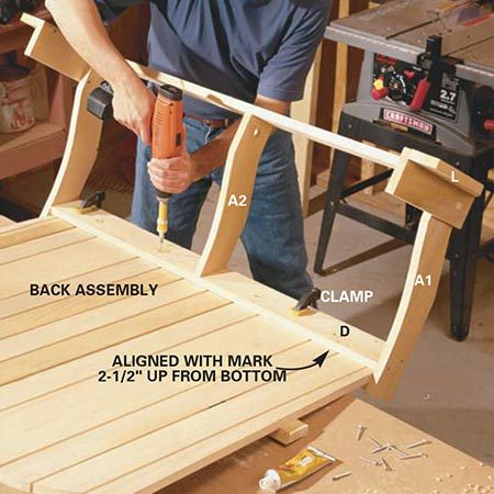 <b>Photo 7: Join the back and seat assemblies</b></br> <p>Hang the lower part of the back assembly over the edge of the work surface to make room as you slide the seat assembly onto it. Align the rear stringer of the seat assembly with a mark drawn 2-1/2 in. from the bottom of the back assembly. Glue the joint, then clamp and screw the assemblies together.</p>