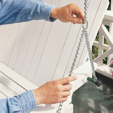 <b>Photo 11: Hang the swing</b></br> <p>Hang the swing securely using special quick-link eyes to join the lengths of chain. The swing should tip back slightly at the arms (about 1 in. from back to front) when the swing is at rest.</p>