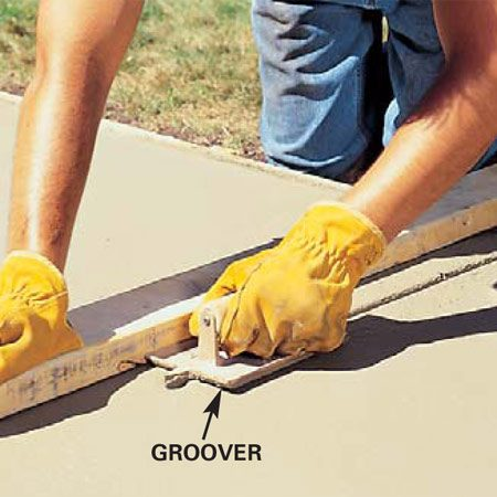 <b>Cut control joints about 1 in. deep</b></br> Control joints should be cut about one fourth the thickness of the slab during the finish-troweling process. Concrete shrinks slightly as it cures and will crack at regular intervals. You want the cracks to occur at the control joints. Space the joints about every 4 ft. on walks and at least every 10 ft. on larger slabs. If the concrete hardens before you can cut the grooves, cut them the next day with a circular saw and diamond blade.