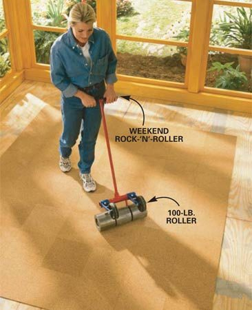 <b>Photo 6: Roll the cork</b></br> Roll the cork down with a rental floor roller. This step is a must to ensure the squares are completely bonded to the underlayment.
