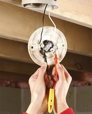 <b>Photo 1: Test for hot wires</b><br/><p>Turn  off the power, remove the light bulb and unscrew the fixture from the electrical  box. Pull the fixture down, but keep your hands away from the wires. Touch one  voltage tester probe to the black wire, and the other to the white wire. If the  voltage indicator doesn&rsquo;t light up, the power is off. </p> <p><strong>Caution: </strong>Turn off power at the main panel. </p>