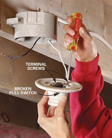 <b>Photo 2: Disconnect the wires</b><br/>Loosen the terminal screws and unhook the wiring from the old fixture. If the wire ends are broken or corroded, strip off 3/4 in. of sheathing, and bend the bare wire end into a hook.