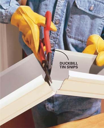 <b>Photo 1: Cut the gutter</b></br> Cut the front and back sides with a tin snips. Bend the gutter and cut the bottom.
