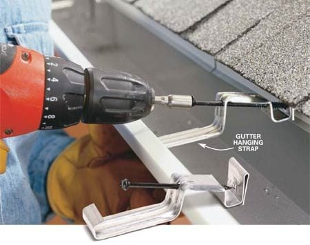 <b>Photo 12: Hook on gutter hanging straps</b></br> Hook a hanger under the front lip of the gutter and screw it through the flashing into the fascia. (The gutter apron will prevent you from slipping the hangers over the back edge of the gutter as intended.) Install hangers every 2 ft.