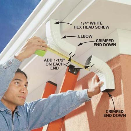 <b>Photo 13: Attach elbows to the downspout</b></br> Screw an elbow to the downspout outlet. Hold another elbow against the wall and measure between them. Allow for a 1-1/2 in. overlap at each end. Use a hacksaw to cut this length from the uncrimped end of a downspout tube.