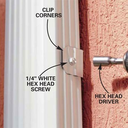 <b>Photo 16: Attach the downspout to the brackets</b></br> Drive screws through the brackets into the assembled downspout. Complete the assembly by adding a length of downspout tube to the bottom elbow to direct water away from the foundation.