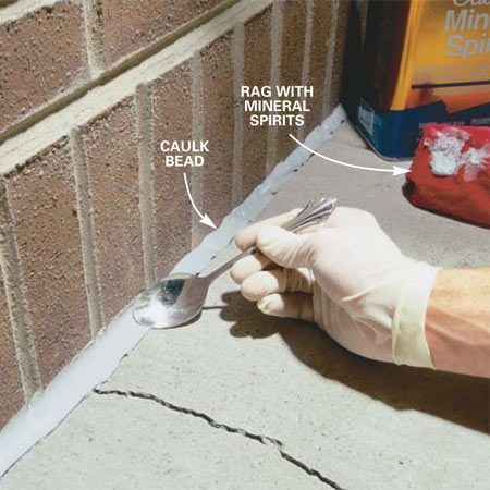 <b>Photo 2: Fill and smooth the joint</b></br> Fill the crack with urethane caulk. Snip the opening of the tube at a 30-degree angle, making the opening the same size as your gap. Use a smooth, even motion, filling the crack flush with the surface, beveling it if it's against the house. Smooth the caulk in wide joints with the back of an old spoon. Wipe the spoon clean as needed with a rag and mineral spirits.