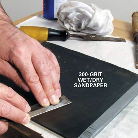 <b>Photo 2: Flatten the back</b><br/><p>Remove any round-over or nicks on the backside of the chisel blade by rubbing in a circular motion. Flatten the back of the blade with 300-grit wet/dry sandpaper taped to a 1/4-in. section of plate glass. (Check with local glass companies for small, scrap pieces.)</p>