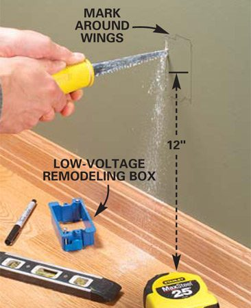 <b>Photo 5: Cut outlet openings</b></br> Hold a low-voltage remodeling box against the wall between two studs so the center of the box is 12 in. above the floor (or match the heights of other outlets in the room) and draw around the box and holding wings. Then cut out the opening with a drywall saw.
