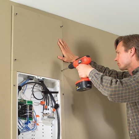 <b>Photo 18: Install a cover panel</b></br> Cut, rout and paint 18-in. wide MDF cover panels and screw them through the drywall into the studs with 2-in. drywall screws and finish washers.