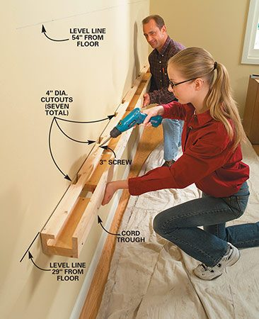 <b>Photo 1: Draw level layout lines</b></br> Mark out on the wall two 10-ft. long level lines: one 29 in. and the other 54 in. from the floor. Mark the location of the studs along each line using a stud finder. Preassemble the cord-management trough according to the plan dimensions. Hold it up to the 29-in. horizontal line and drive 3-in. screws into each stud.