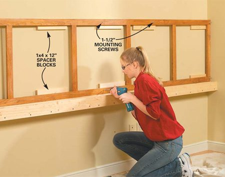 <b>Photo 2: Screw the corkboard frame to the spacer blocks</b></br> Glue and screw 12-in. 1x4 pine spacer blocks to the wall studs along the cord trough and just under the 54-in. horizontal line. Position them so they line up with the centered mounting screws on the bulletin board frame. Set the preassembled corkboard frame onto the trough, then drive 1-1/2 in. screws into the 1x4 blocks.