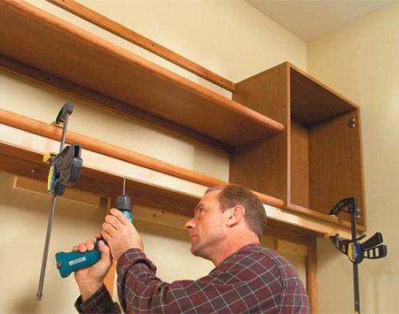 <b>Photo 7: Screw the light valance to the shelf</b><br/>Clamp the 3/4 x 1-1/2 in. light valance to the cabinets and shelf. Hold it 1-1/2 in. back from the cabinet fronts. Drill clearance and countersink holes every 2 ft., then drive 2-in. screws into the cabinets and the lower shelf to secure it. Countersink screwheads slightly and then cover them with self-adhering caps. Caps are available in a variety of colors and wood finishes.
