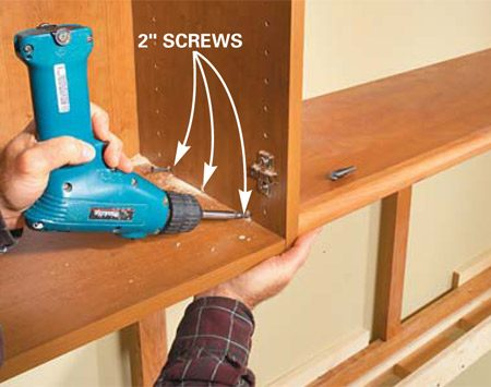 <b>Photo 6: Install the lower shelf</b></br> Set the lower shelf on the corkboard frame, holding the front edge flush with the bottom of the cabinet. Then drive three 2-in. screws to fasten it in place. Install the middle shelf the same way.