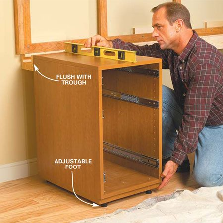 <b>Photo 8: Level the first base cabinet</b></br> Push the left drawer base cabinet into place flush with the end of the cord trough. Adjust the feet to level it with the trough. Drive two 1-1/2 in. screws through the back into the trough.