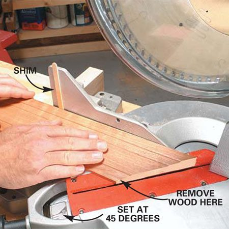 <b>Photo 1: Shim the piece being cut</b></br> Close a gap on the top of a miter by placing a skinny (1/16-in. or less) shim against the portion of the fence farthest from the blade. Slide the molding tight to the shim and against the fence near the blade. Hold it in this position while you make the cut. <strong>Caution</strong>: Keep your fingers at least 6 in. from the path of the blade.